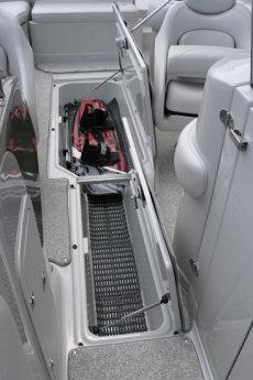 Crownline Deck Boat 262 EX - Convenient wakeboard storage between driver and passenger seats